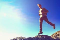 Man jumping over gap on mountain hike Stock Photos