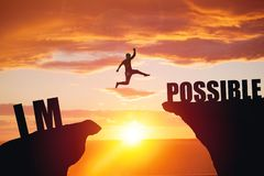 Man jumping over impossible or possible over cliff on sunset background stock photo