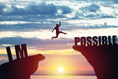 Man jumping over impossible or possible over cliff on sunset background royalty free stock photos