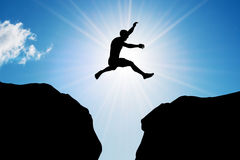 Man jumping over precipice. Risk, challenge, success. Man jumping over precipice between two rocky mountains at sun light. Freedom, risk, challenge, success Royalty Free Stock Photography
