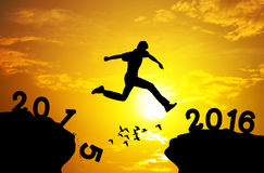 Man jumping over precipice on sunset background. New year 2016 royalty free stock photos