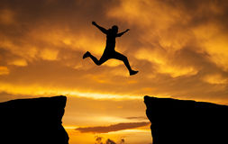 Man jumping over rocks with gap on sunset fiery background. Element of design Stock Image