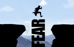 Man jumping over text FEAR. royalty free stock photo