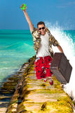 Man jumping over the waves. A young, attractive male in a colorful outfit in a tropical island setting as a stereotype tourist royalty free stock photography