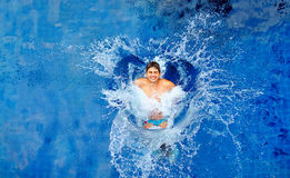Man jumping in pool, huge splash, top view Royalty Free Stock Images