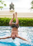 Man jumping into the pool. Man jumping into the outdoor swimming pool Royalty Free Stock Image