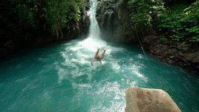 Man jumping in the river with waterfall slow mo. Back view: young man jumping from the rock hill in the river slow motion at background tropical waterfall stock video