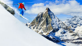Man jumping from the rock, skiing on fresh powder snow with Matt Stock Images