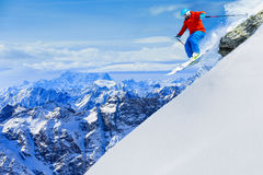 Man jumping from the rock, skiing on fresh powder snow. Stock Photo