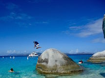 Man jumping from rock in Virgin Islands. Man jumping from rock into water in the Virgin Islands in Carribean Royalty Free Stock Image