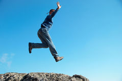 Man jumping on the rocks Stock Images