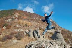 Man jumping on the rocks Stock Photo