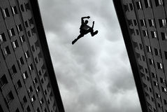 Man jumping from roof to roof Royalty Free Stock Photography