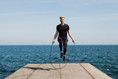 Man with jumping rope on pier. Young sportive man doing rope jumping on concrete pier with sea on background Stock Image