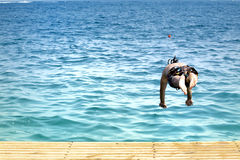 Man jumping in the sea. Man jumping in the blue sea Royalty Free Stock Photos