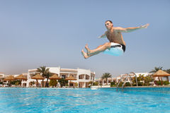 Man jumping in swimming pool. Low angle view from the swimming pool Royalty Free Stock Photography