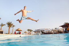 Man jumping in swimming pool. Low angle view from the swimming pool Stock Photos