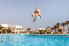 Man jumping in swimming pool Stock Photo