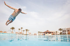 Man jumping in swimming pool. Low angle view from the swimming pool Stock Photo