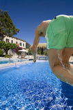 Man jumping into swimming pool with chateau hotel in background Royalty Free Stock Photography