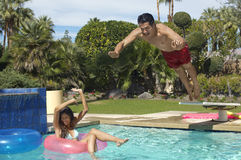 Man Jumping Into Swimming Pool Over Woman On Ring. Happy young men jumping into swimming pool over women on inflatable raft Stock Photography