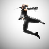 Man jumping with a sword, attack. Man jumping with a sword in a suit of the warrior Royalty Free Stock Image