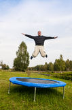 Man jumping on the trampoline. Seems higher tree Stock Images