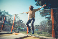 Man jumping on trampoline at playground Stock Images