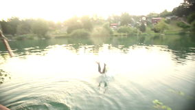 Man jumping from a tree into river at sunset. Handsome african american man jumping from a tree into river at sunset, graded, in slow motion stock footage