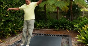 Man jumping up and down on bouncing trampoline 4k. Man jumping up and down on bouncing trampoline in garden 4k stock video footage