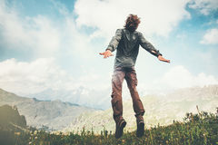 Man jumping up at mountains to clouds sky Royalty Free Stock Images