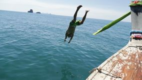 Man Jumping In Water From Long Tail Boat Nose Back Rear View, Young Tourist On Sea Vacation In Thailand