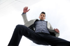 Man jumping and wearing jacket and shirt Stock Image