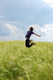 Man jumping in wheat field. Side view of trendy young man jumping in countryside wheat field Stock Image