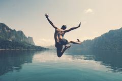 Free Man Jumping With Joy By A Lake Stock Image - 124903651