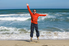 Man jumps. In red t-shirt on sand on seashore stock images