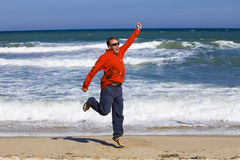 Man jumps. In red t-shirt on sand on seashore Royalty Free Stock Image