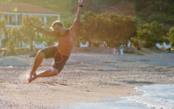 Man jumps on a beach Stock Photography