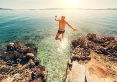 Man jumps in blue sea lagune water Stock Photography