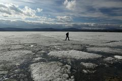 Man jumps on the ice during the ice drift on the lake stock photos