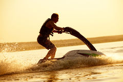 Man jumps on the jetski Royalty Free Stock Image