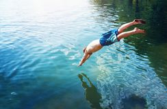 Man jumps like fish into the water of the lake, swims, enjoys spending time on summer holidays stock images