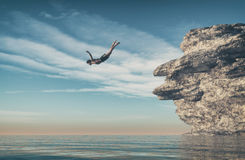 Man jumps into the ocean from a cliff. This is a 3d render illus Stock Photo