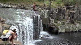 Man jumps off Charlies Rock waterfall in Kerikeri, New Zealand stock video footage