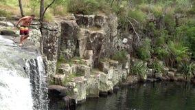 Man jumps off Charlies Rock waterfall New Zealand stock video
