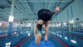 Professional swimmer with prosthesis jumps in a pool, back view.
