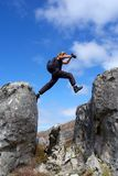 Man jumps from rock. Man with long hair jumps from rock - low angle, against sky. Shot in Hottentots-Holland Mountains nature reserve, near Grabouw, Western Cape royalty free stock image