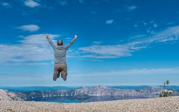 Man Jumps on Rocky Overlook to Crater Lake. On Summer morning Stock Photography