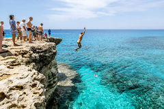 Man jumps into sea from a cliff at Cape Greco . Cyprus. Stock Images