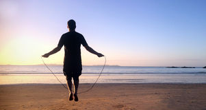 Man jumps on skipping rope in the beach Royalty Free Stock Images